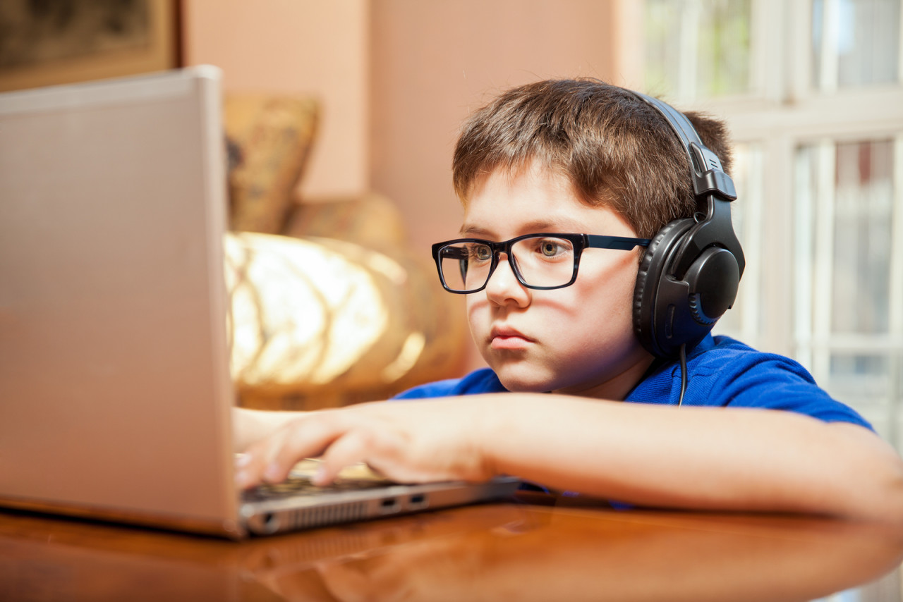 Tween gamer wearing glasses and headphones playing a videogame on a laptop